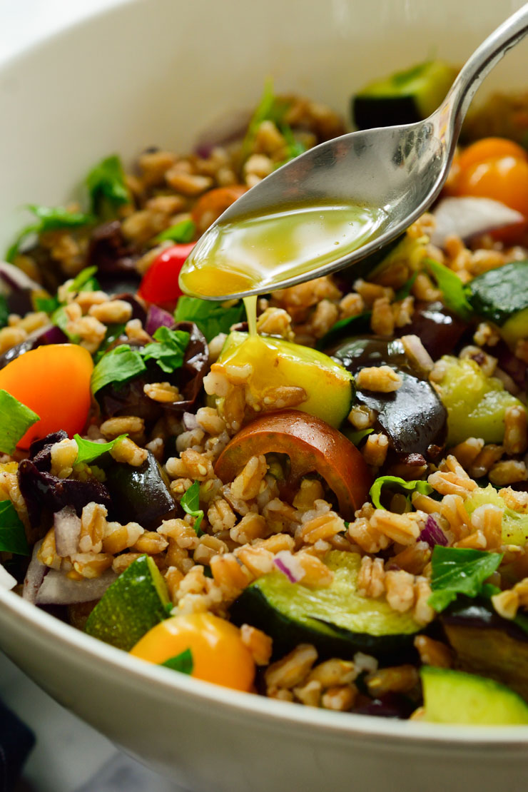 Drizzling vinaigrette over the tossed farro salad.