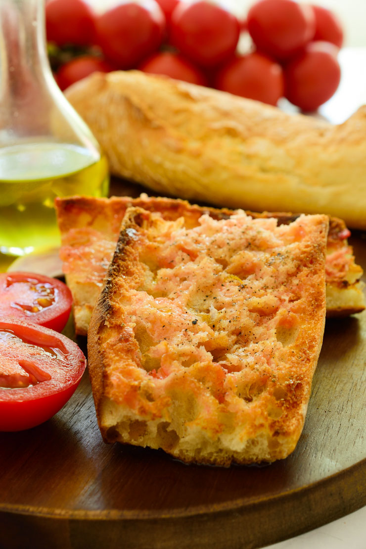 Pan con tomate with bread, olive oil and tomatoes in the background.