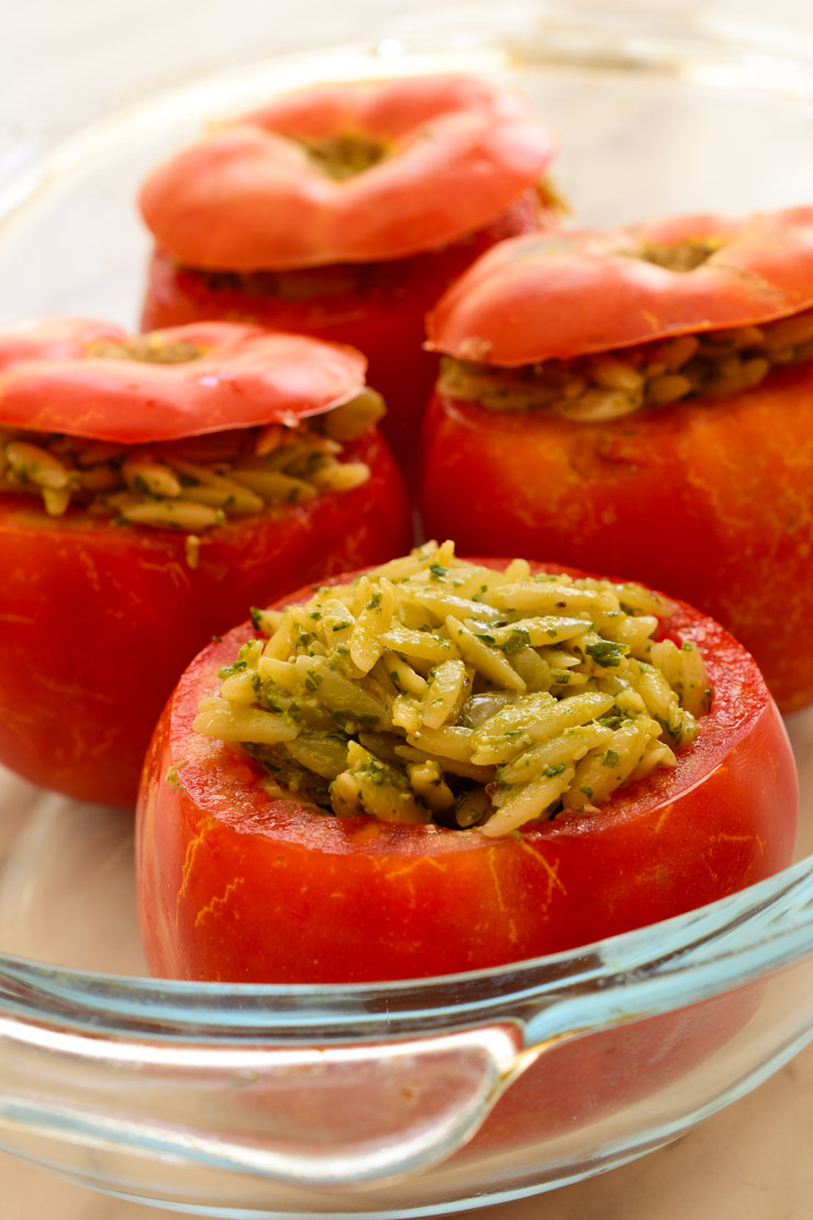 Unbaked pesto orzo stuffed tomatoes in a baking dish.