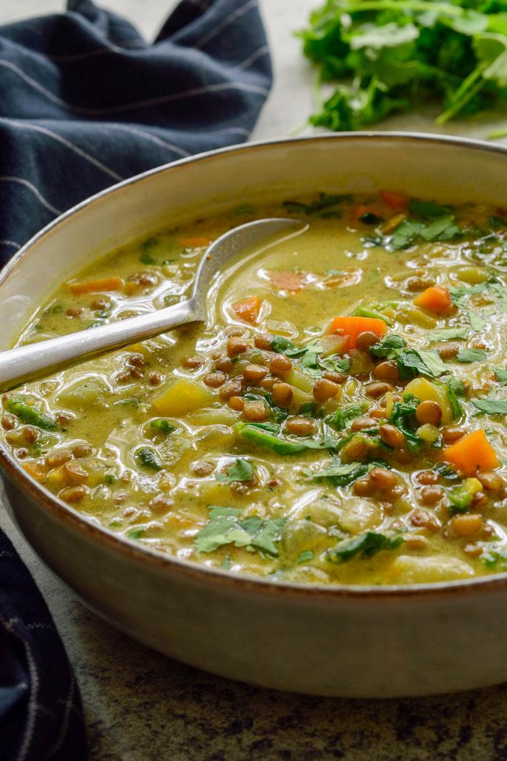Un bol de la sopa de lentejas al curry con una cucharada.