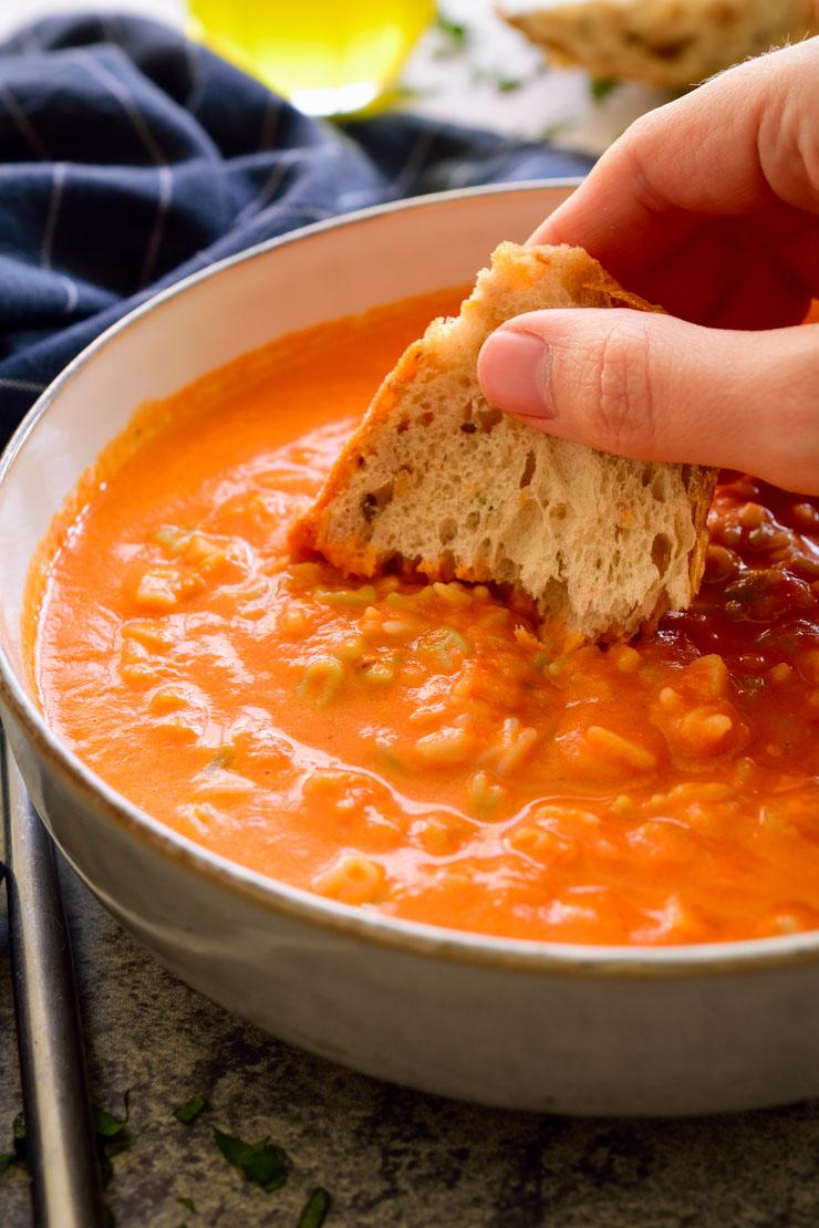 Una mano remojando pan en un bol de sopa de tomate.