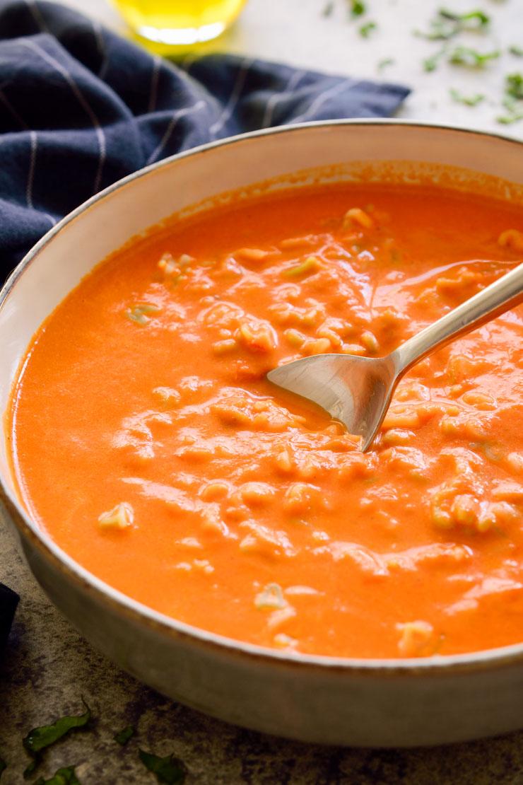 Un bol de sopa de tomate con pasta y una cuchara.