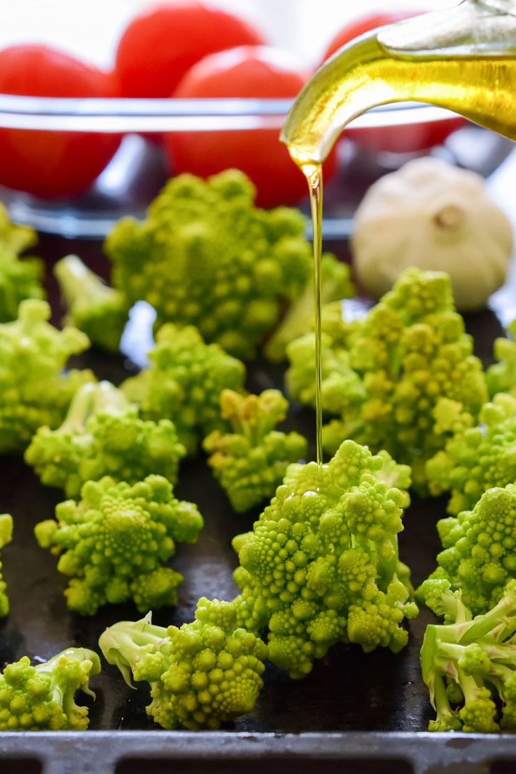 Romanesco florets on a pan with olive oil drizzling over.
