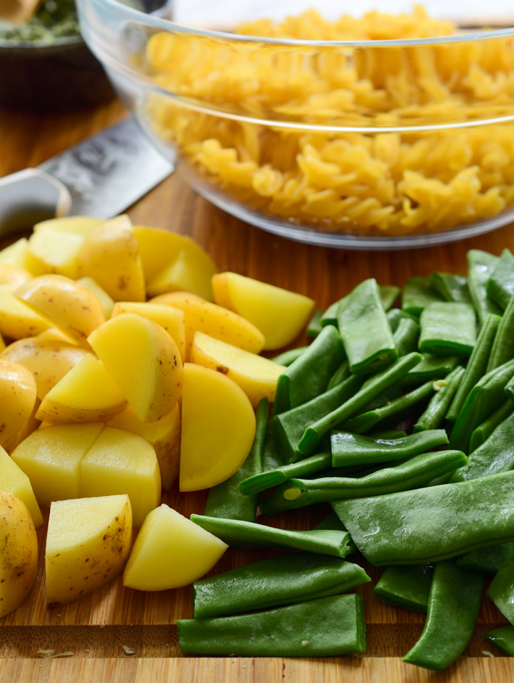The chopped potatoes and green beans on a cutting board with a transparent bowl of dry pasta behind.