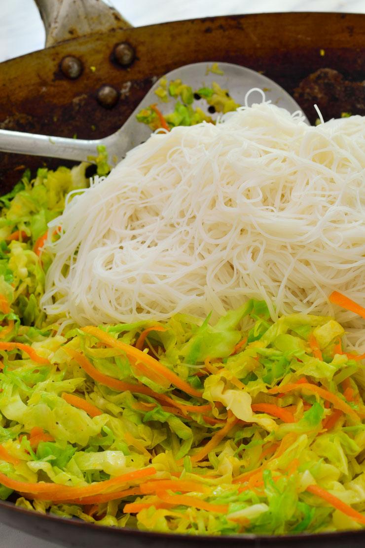 Un wok con las verduras salteadas y los vermicelli encima.