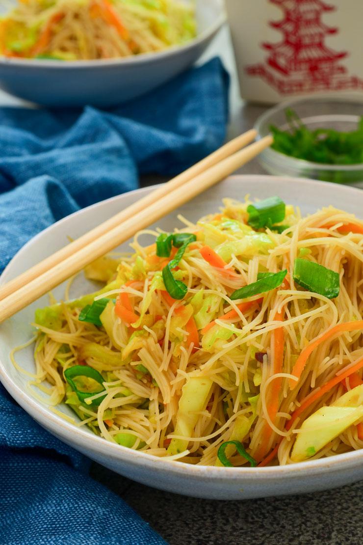 Un bol azul lleno de vermicelli de arroz con verduras salteadas y palitos chinos al lado.