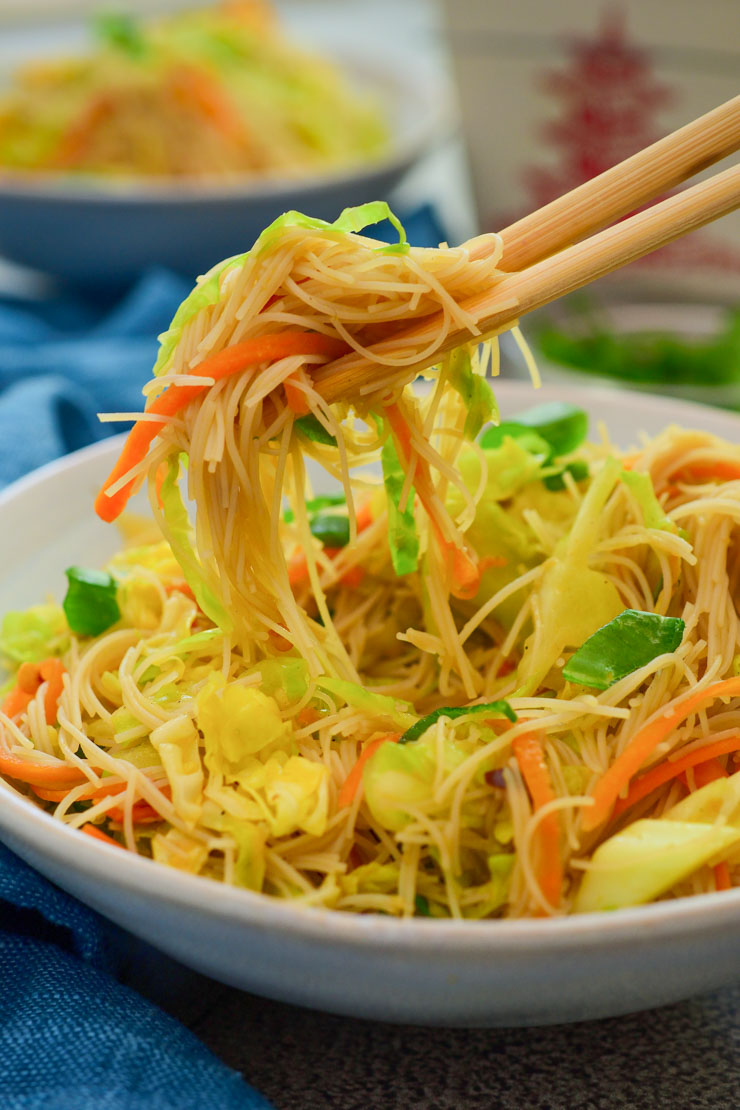 El plato servido en un bol azul y palitos chinos.