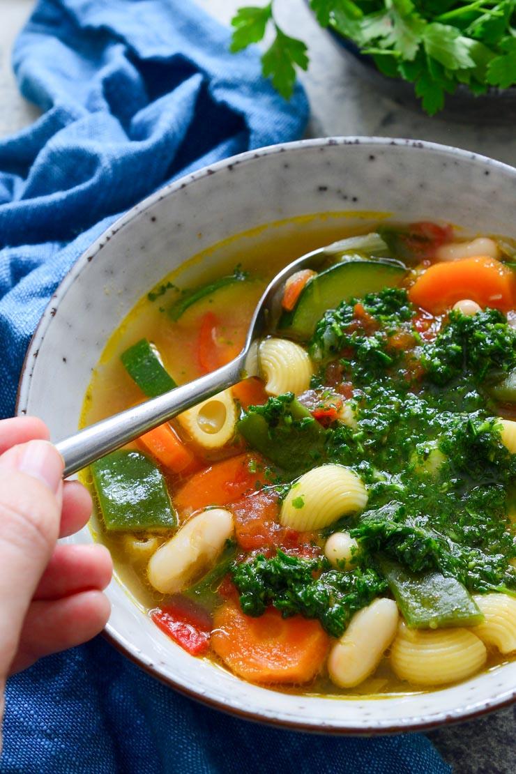 Una foto de la sopa visto desde arriba con la salsa mezclada y una mano cogiendo una cucharada.