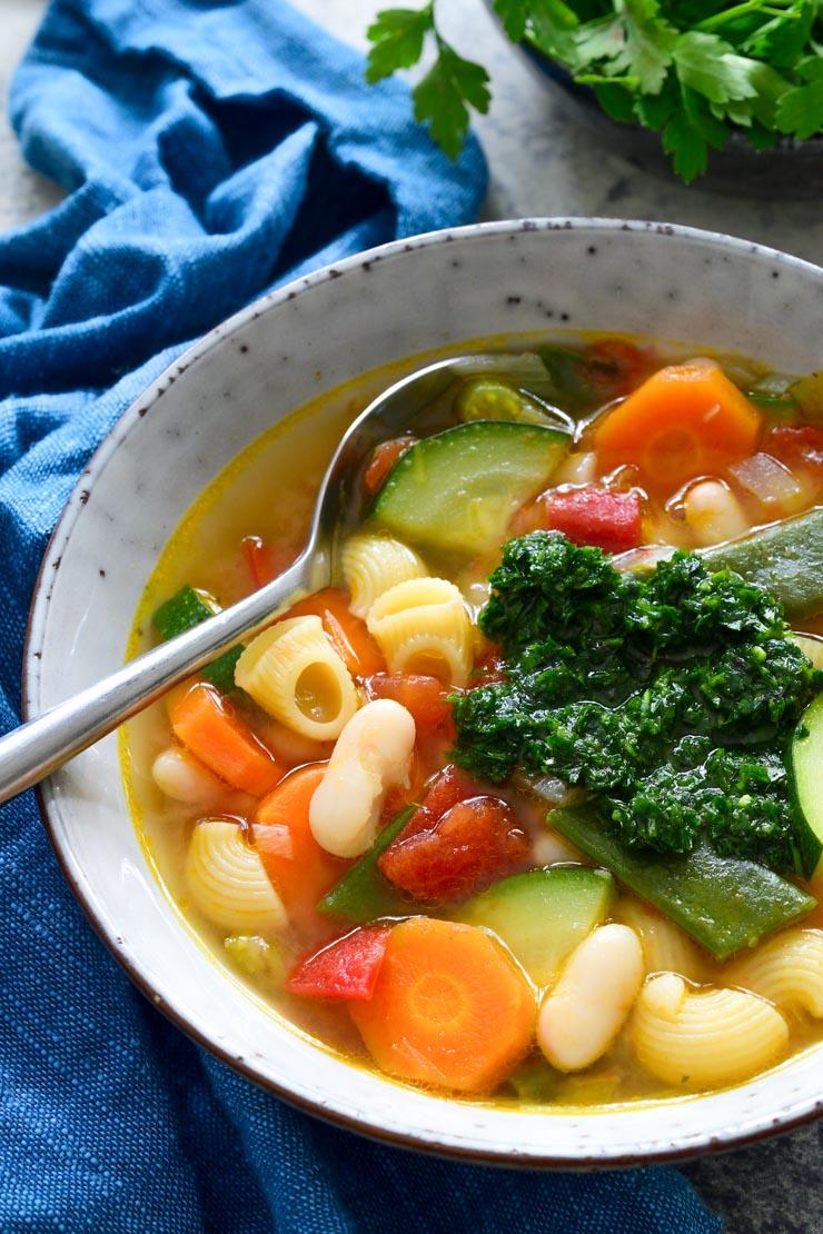 Una foto desde arriba de un bol de sopa de verduras con la salsa pistou encima y una cucharada. Una servilleta azul y hierbas al fondo.