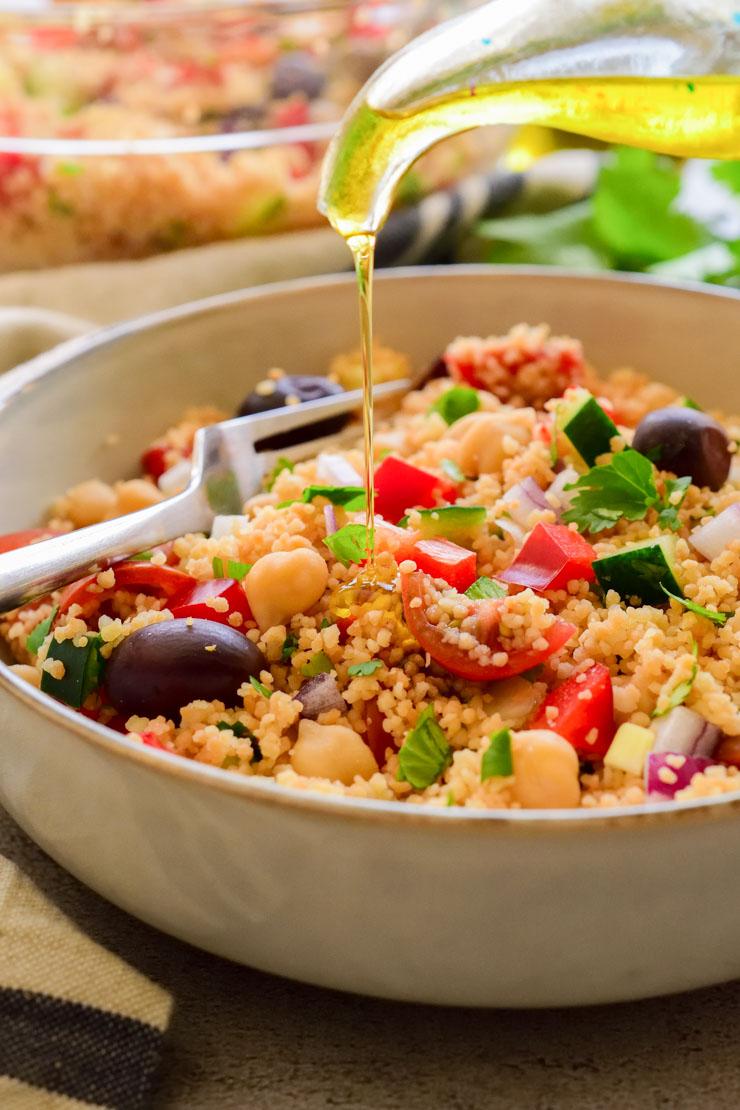 Rociando la ensalada de chucus con aceite de oliva en un bol gris.