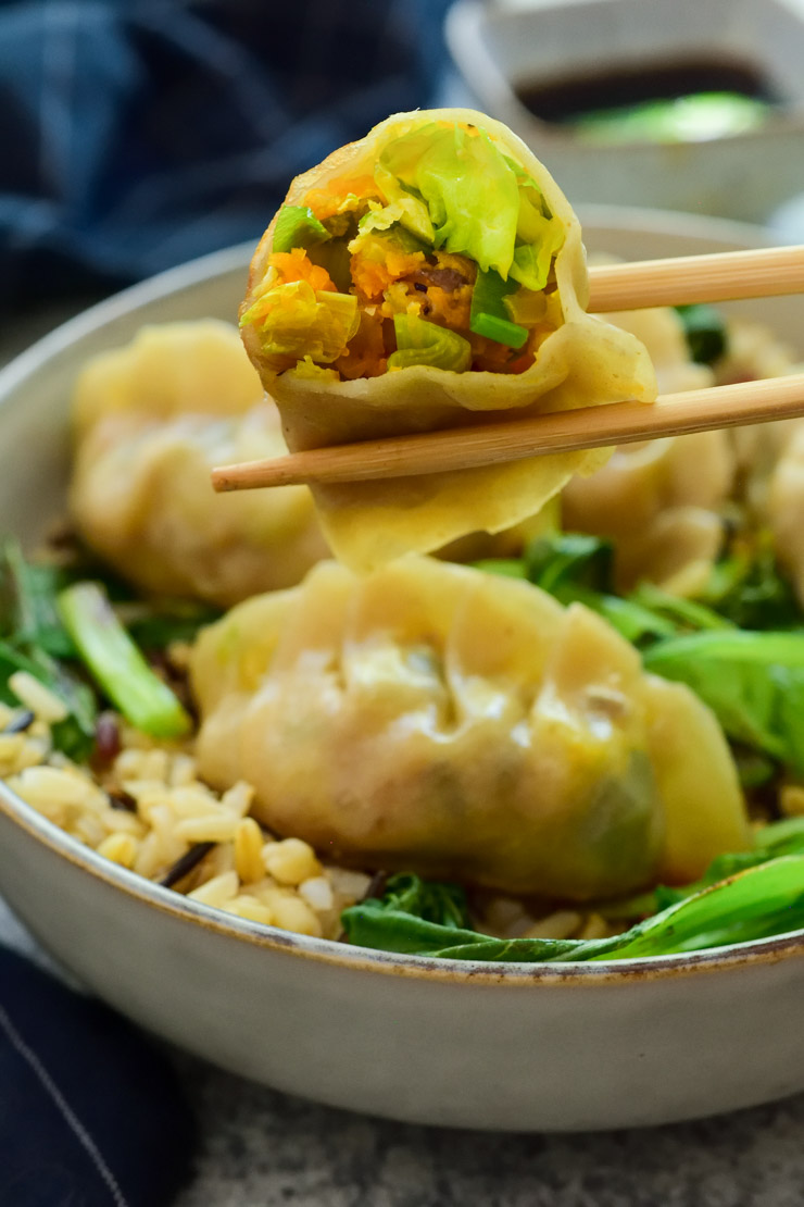 Dos palitos chinos agarrando una empanadilla china cortada para mostrar su relleno. El plato de empanadillas chinas y arroz al fondo.