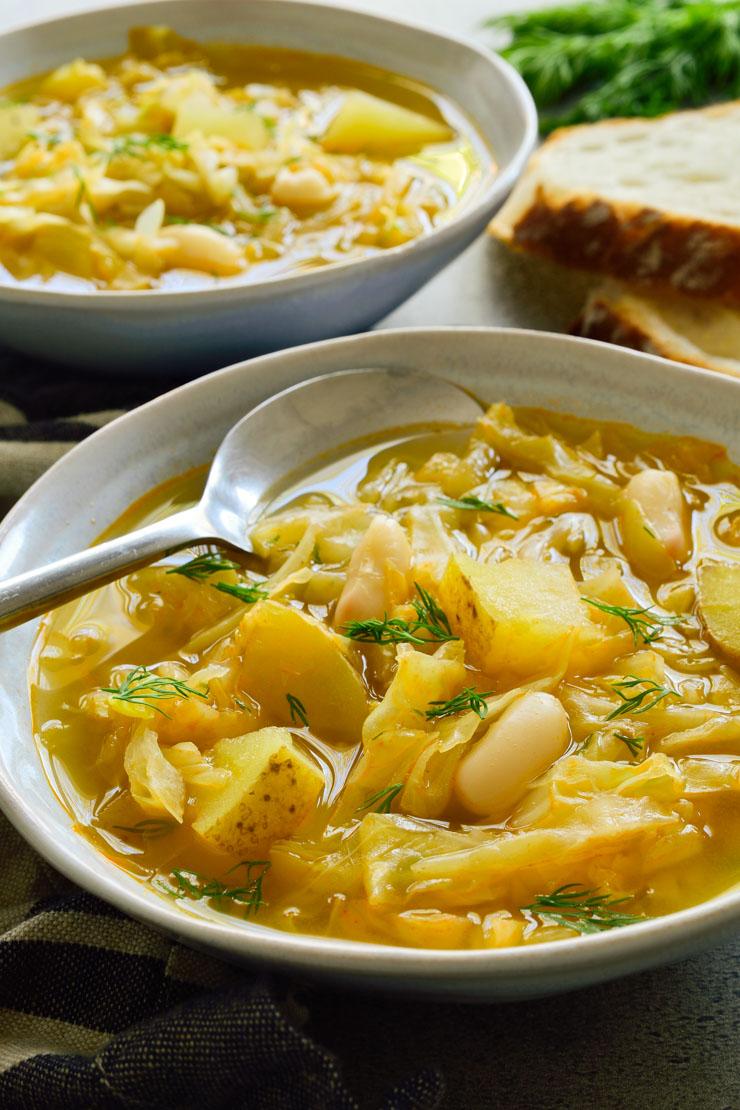 Dos platos grises de sopa de repollo vegetariana con una cuchara.