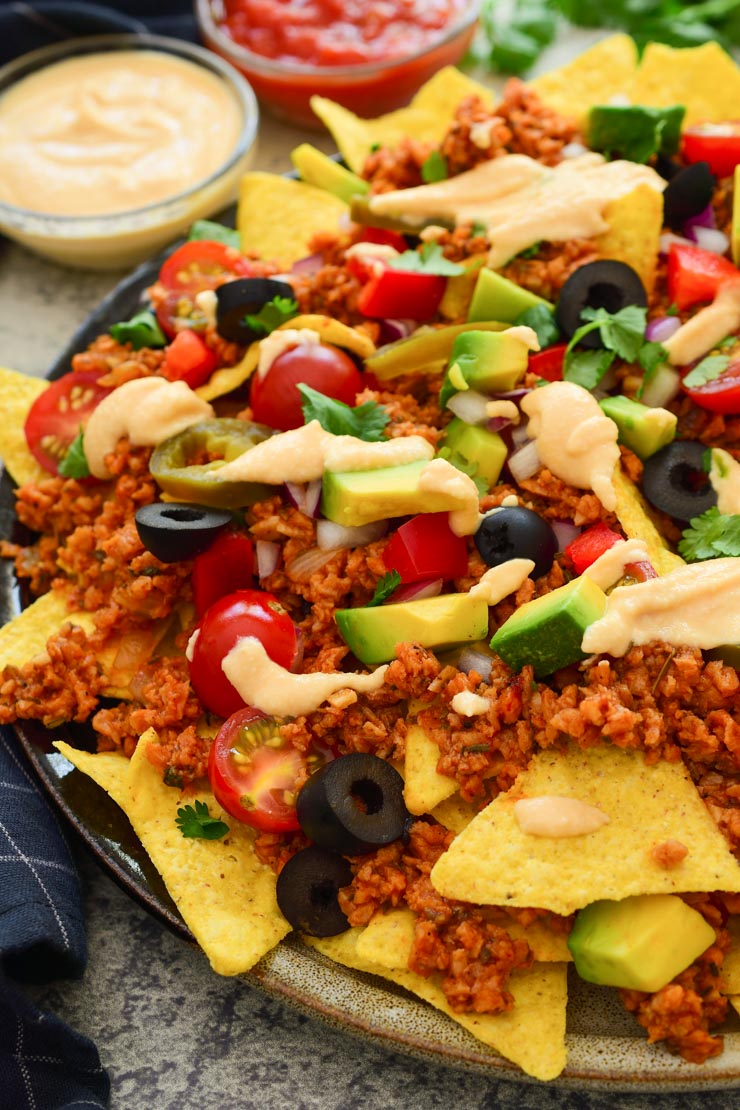 A overhead shot of loaded vegan nachos with nacho cheese.
