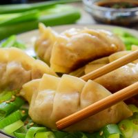 A plate of vegan dumplings. The front one is held by chopsticks. Dipping sauce in the back.