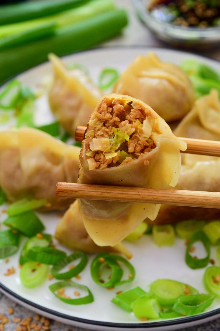 A pair of chopsticks holding up an open vegan potsticker to show the filling.