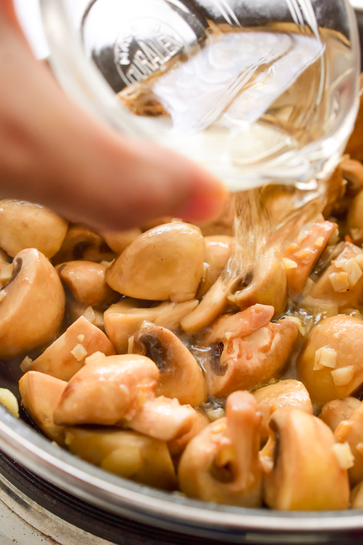 A hand pouring white wine from a clear bowl into the pan with mushrooms.