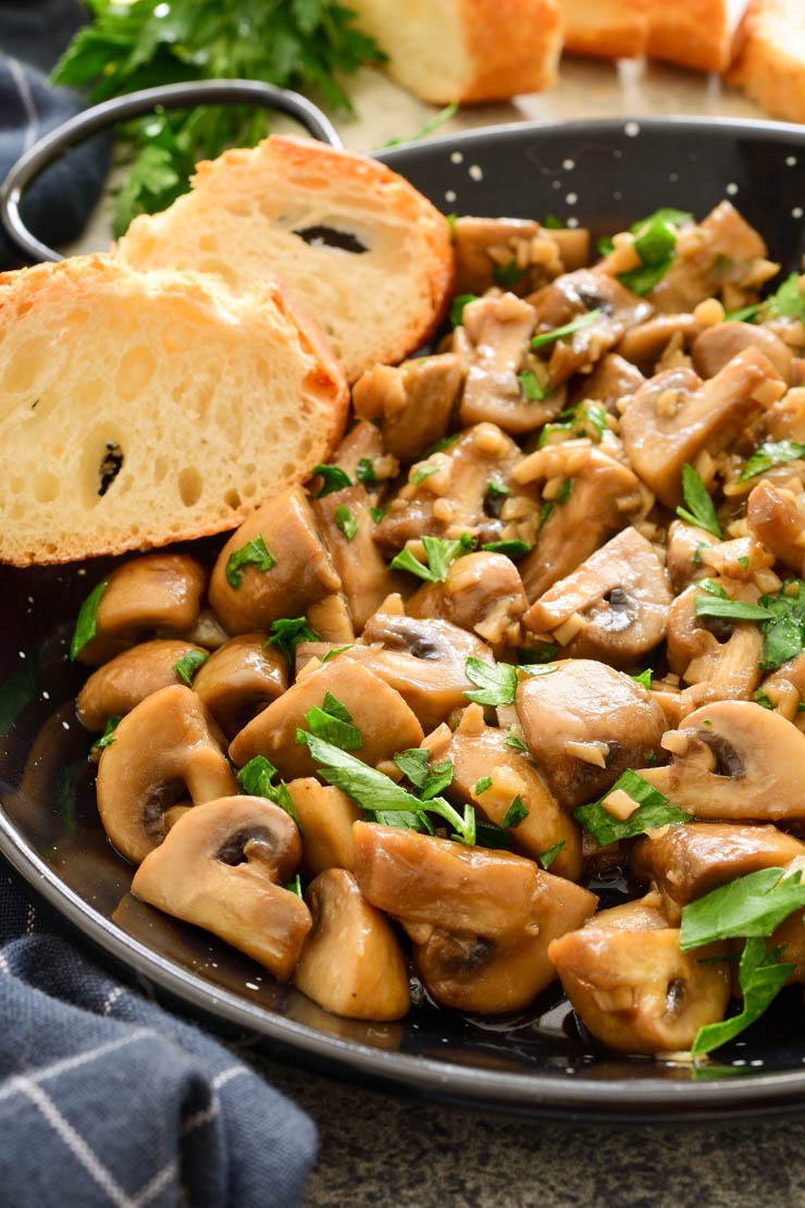 A black pan with cooked garlic mushrooms and two slices of baguette.