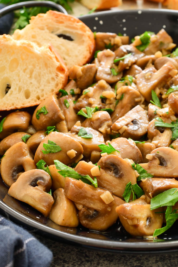A close-up photo of the black pan of garlic mushrooms with two slices of baguette on the side.