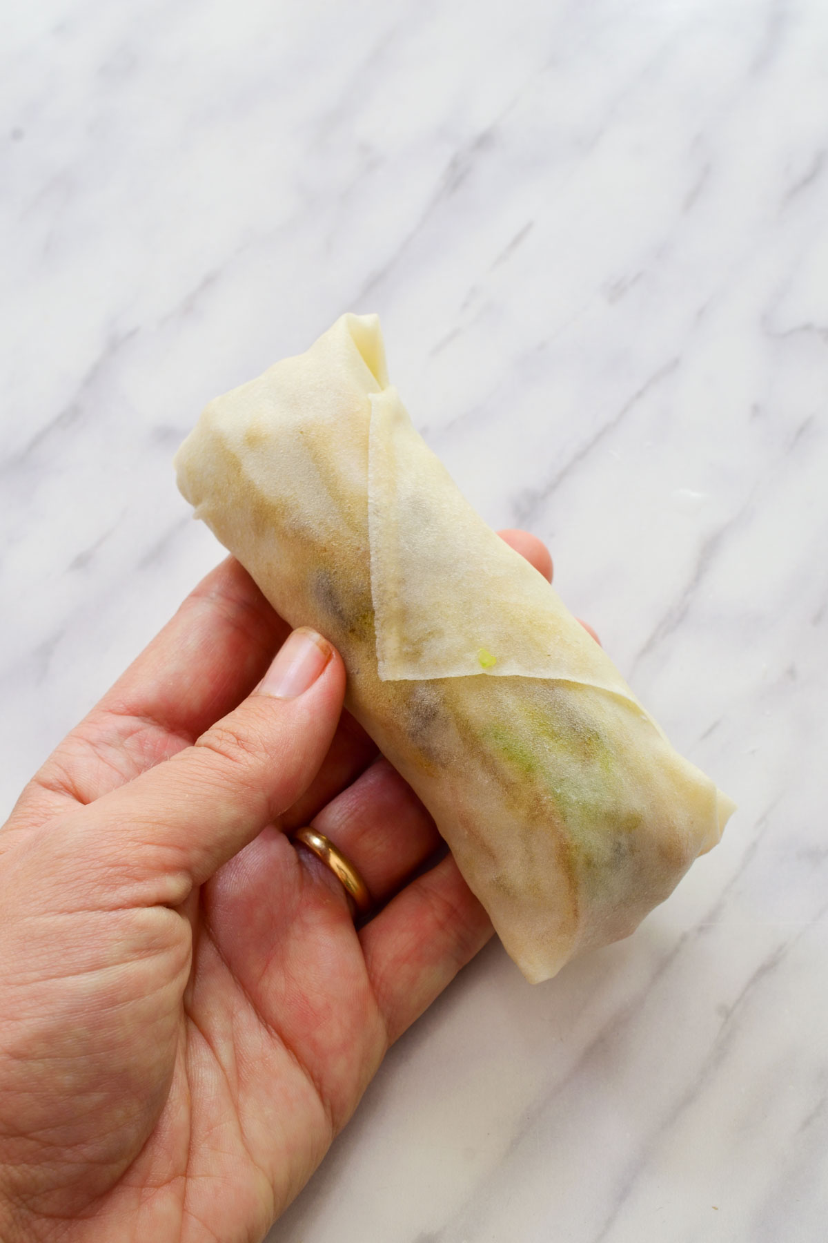 A hand holding the finished spring roll before frying.