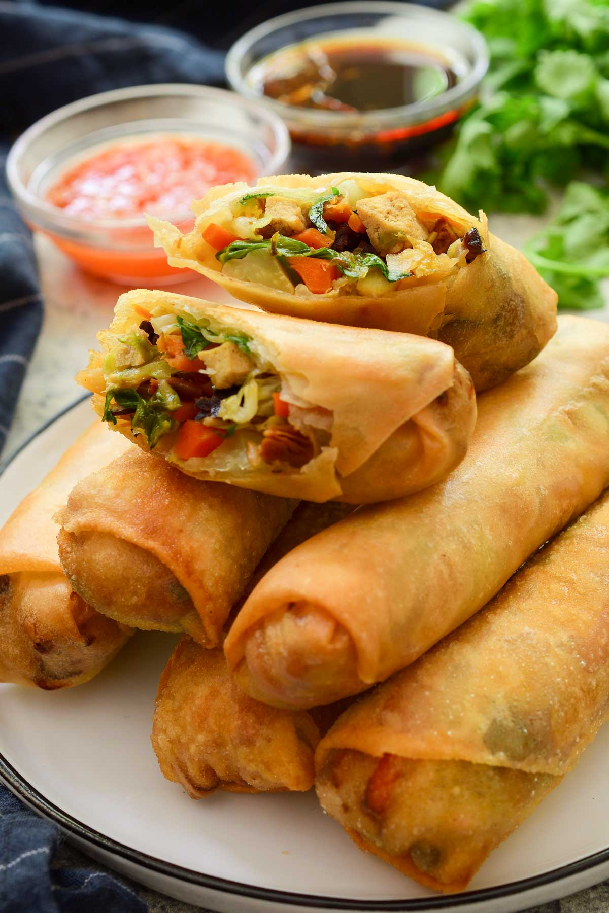 A pile of vegetable spring rolls with one cut open showing the filling. Two dipping sauces in the background.