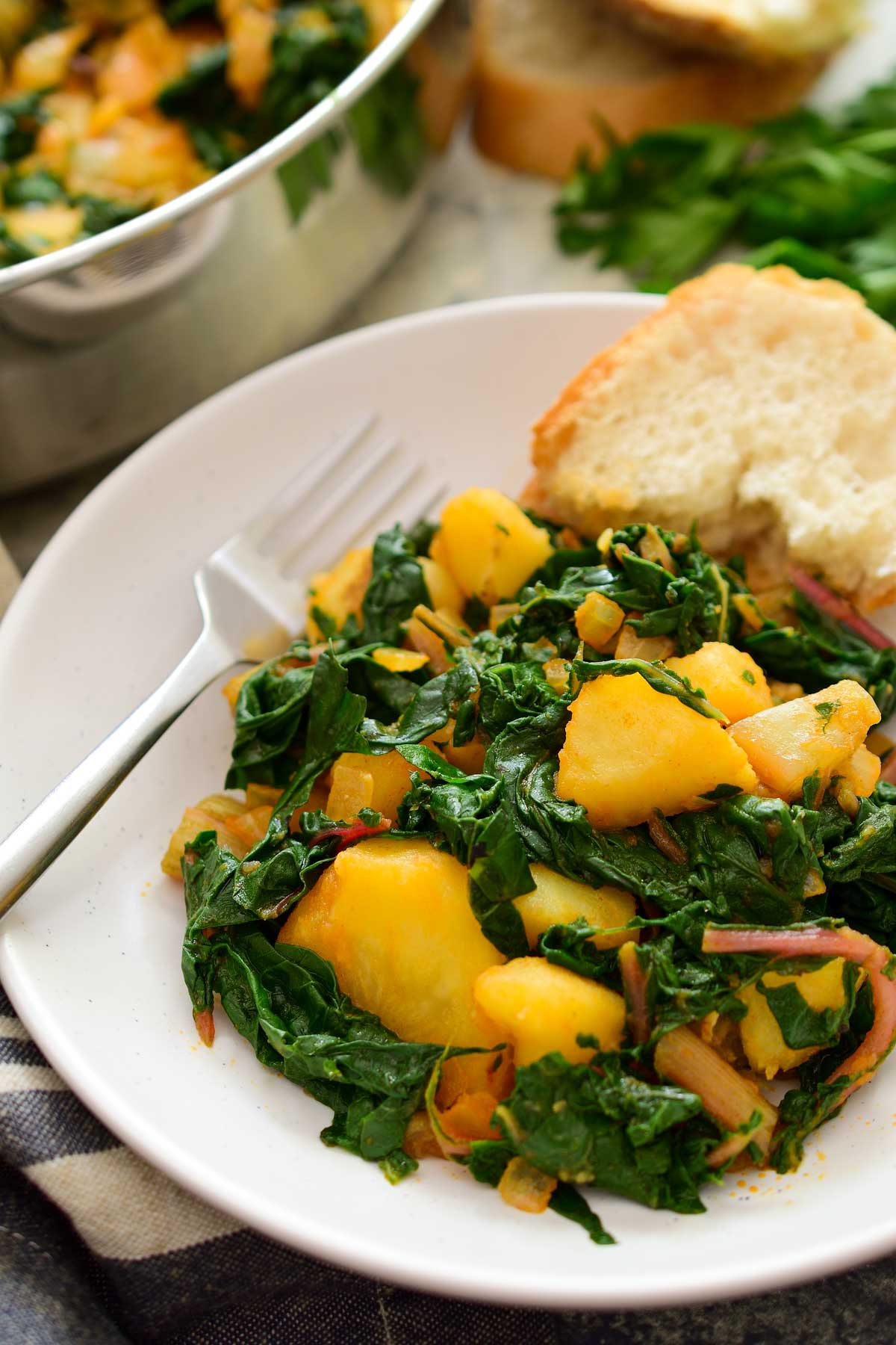 A white bowl with Swiss chard and potatoes, bread on the side.