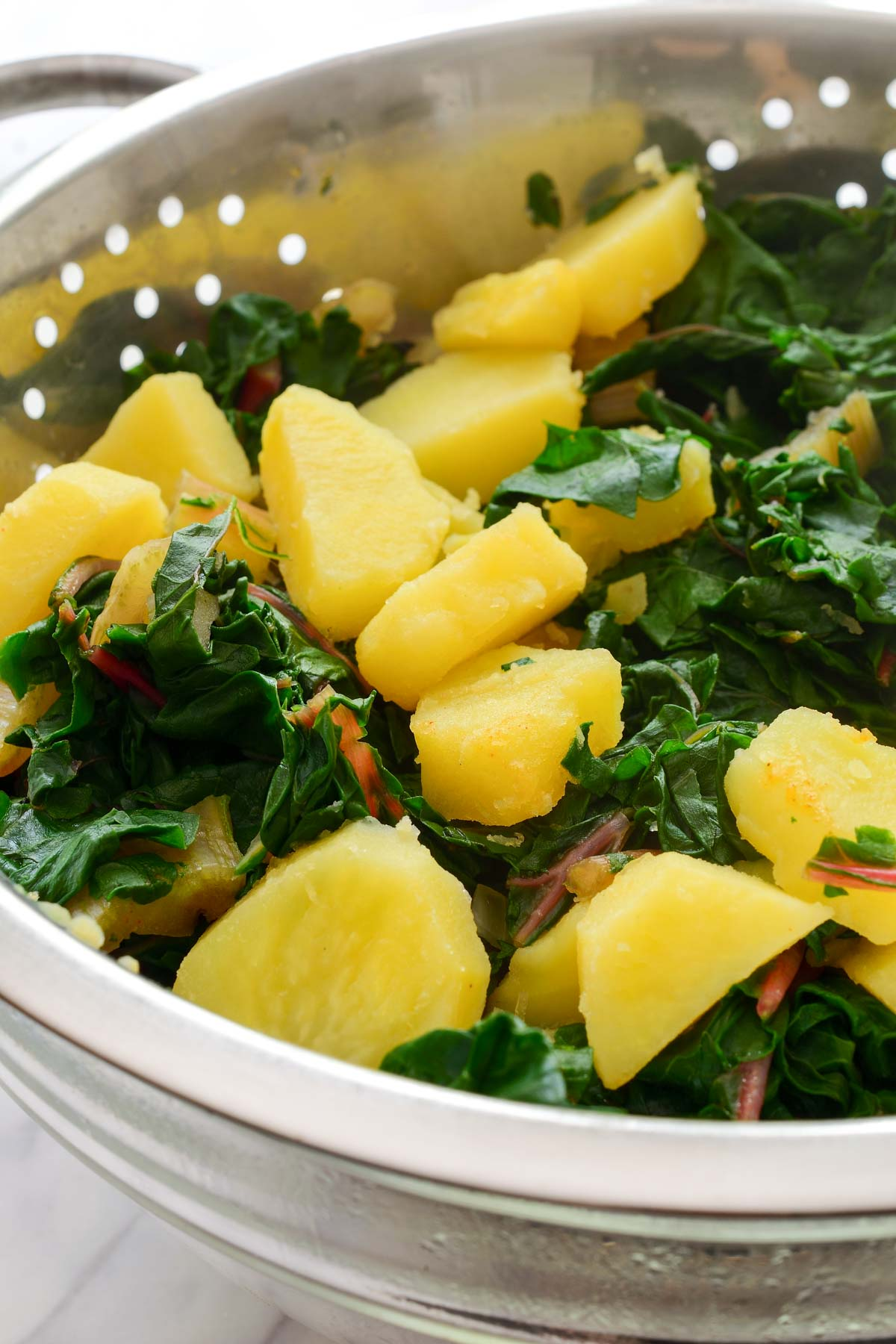 A strainer with the cooked potatoes and chard.