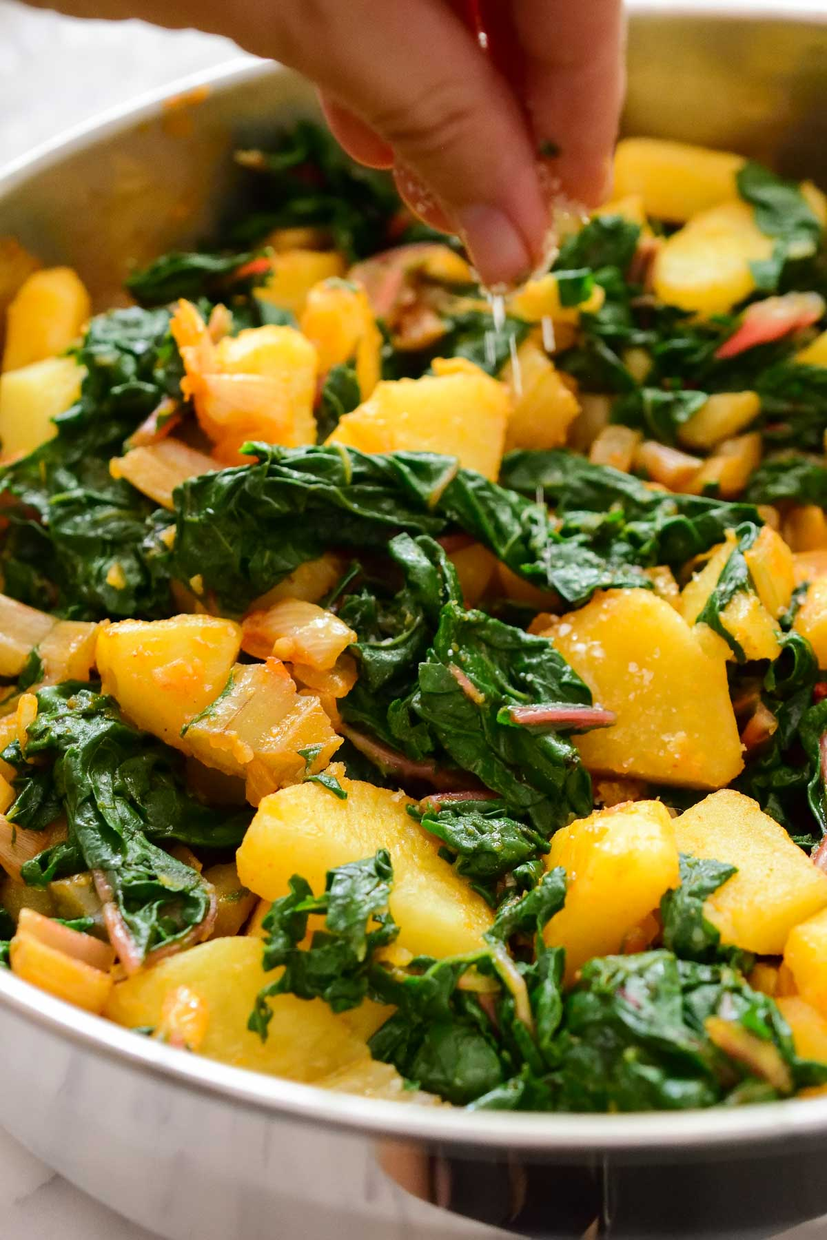 A hand sprinkling salt into the pan of Swiss chard and potatoes.
